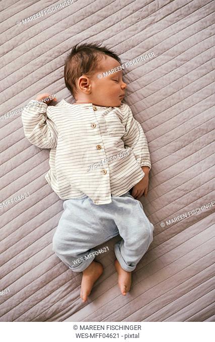 Newborn baby boy sleeping on a blanket