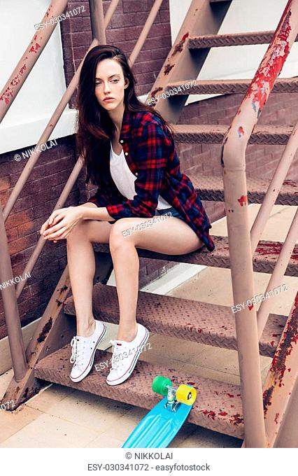 Young beautiful female in checkered hipster shirt and short jeans shorts and white sneakers sit on the stairs with her blue mini skateboard longboard