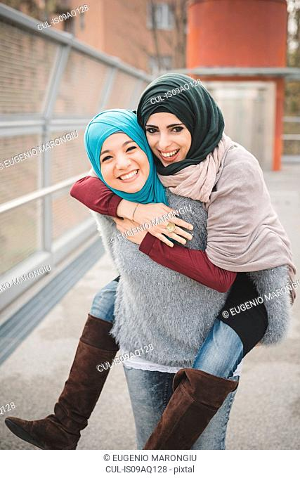 Young woman giving piggyback to friend