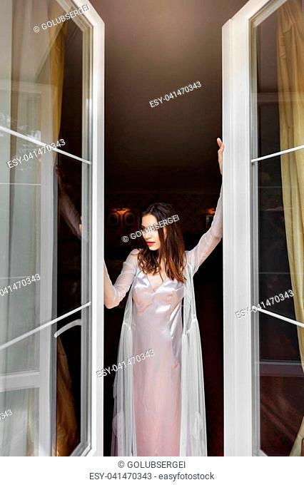 girl in a nightie opens the window