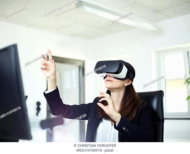 Businesswoman wearing VR glasses in office
