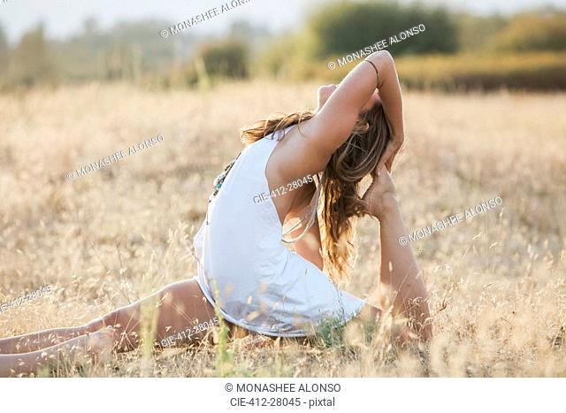 Boho woman in royal king pigeon pose in sunny rural field