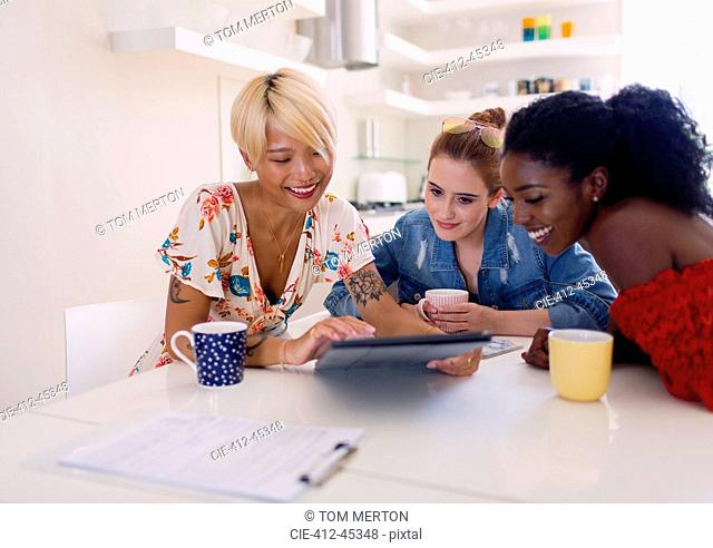 Young women friends drinking coffee and using digital tablet at kitchen table