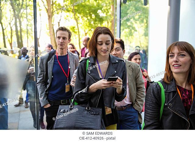 Businesswoman with smart phone arriving, entering doorway