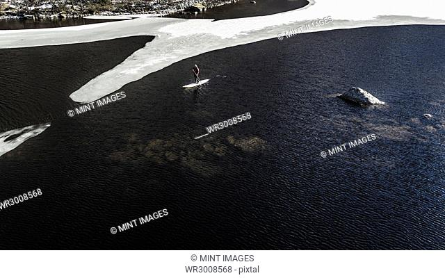 Aerial view of a paddleboarder on the water in an inlet with melting ice floes in the Lofoten Islands, Norway