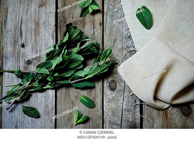 Fresh peppermint and cloth on wooden table, view from above