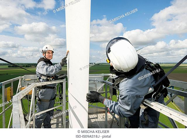 Maintenance work on the blades of a wind turbine, measuring the electrical resistance of a lightning bolt
