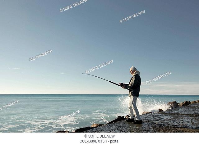 Senior man fishing, Livorno, Italy