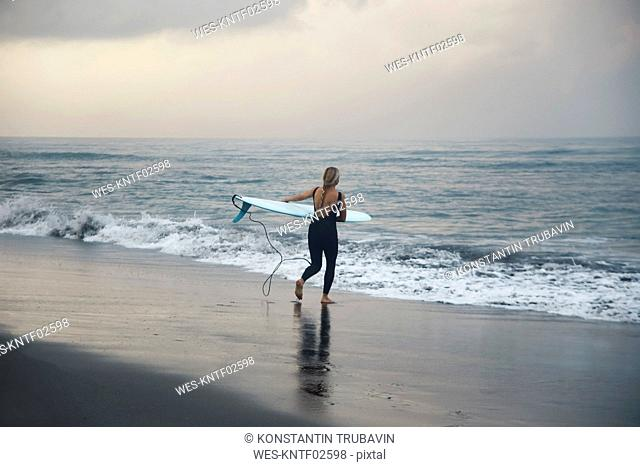 Indonesia, Bali, Canggu beach, surfer with surfboard at the beach