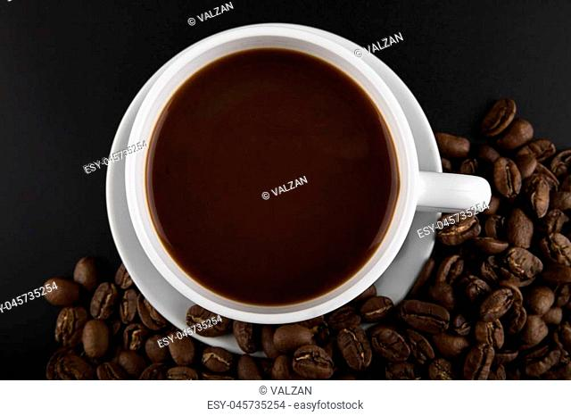 cup with hot coffee and grains on a black background