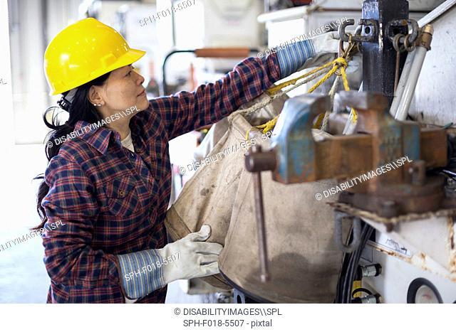 Female power engineer securing equipment on bucket truck