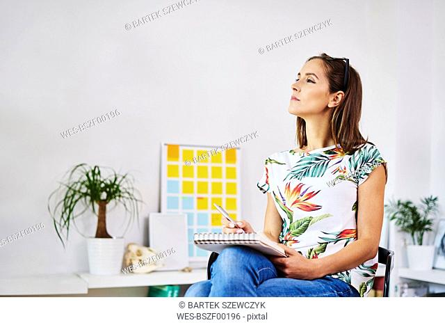 Thoughtful young woman sitting on chair taking notes