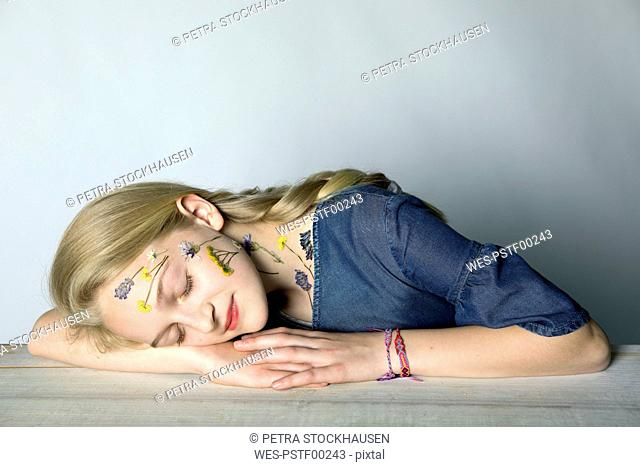 Portrait of blond girl with tattoo of pressed flowers on her face