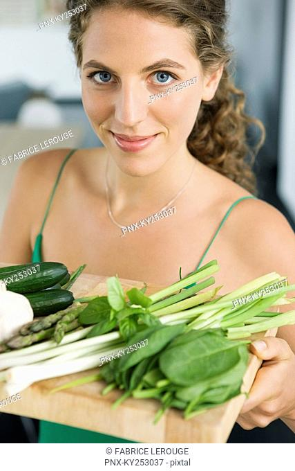 Woman holding vegetables in the kitchen