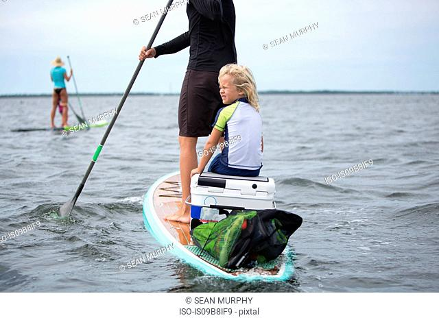 Woman on paddle board with young boy, another paddle boarder in distance