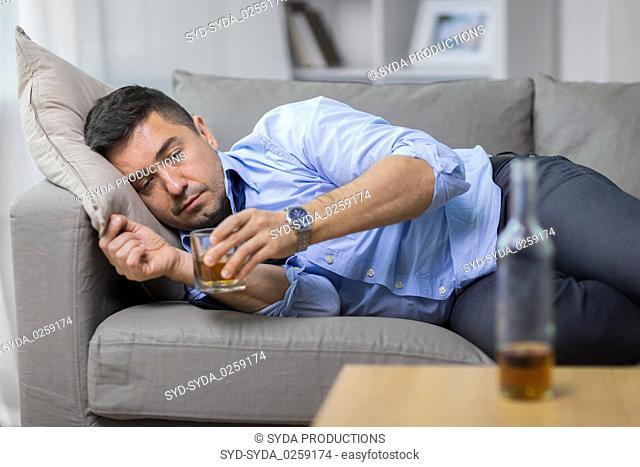 alcoholic lying on sofa and drinking whiskey