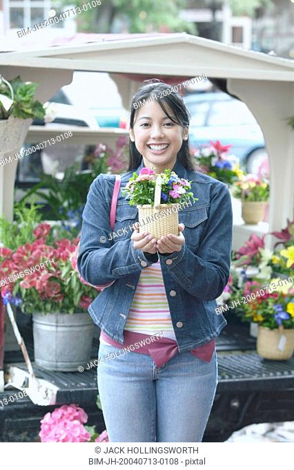 Asian woman holding potted plant