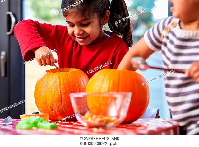 Children gutting pumpkin in kitchen