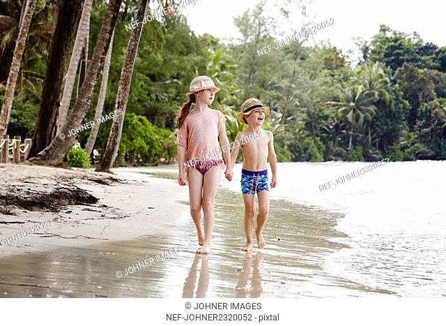 Boy and girl walking on beach