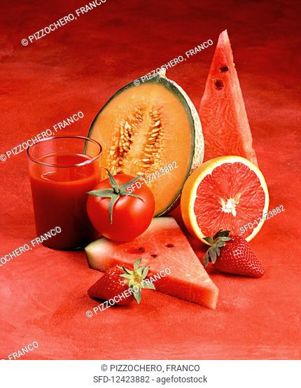 Red fruits, a tomato and a glass of tomato juice