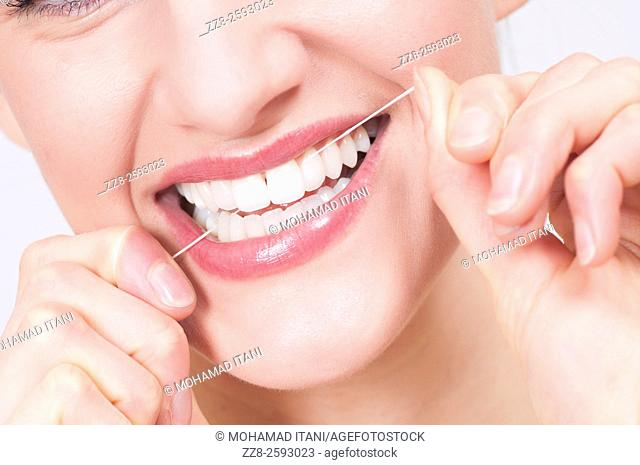 Young woman flossing her clean white teeth