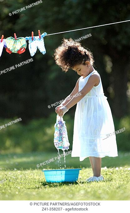 Girl hanging her doll's clothes