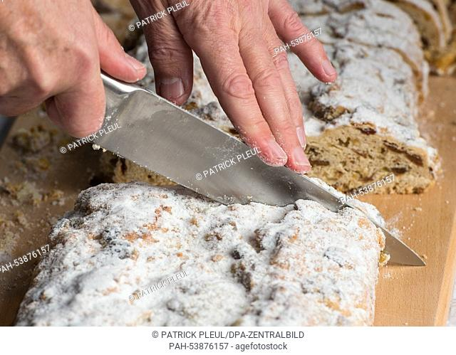 Stollen is cut to be handed out to visiters at the Christmas Market in Cottbus,Germany, 26November 2014. The Christmas Market on the Altmarkt opened today...