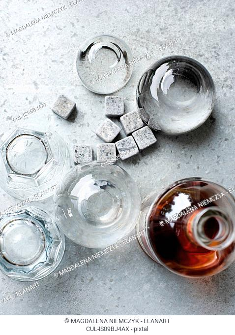 Bottle and glasses with whiskey stones, overhead view