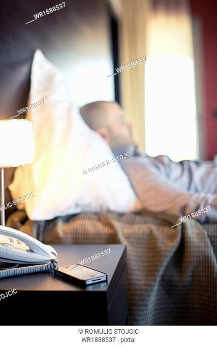 Mobile Phone On Bedstand, Businessman in Background Sleeping, Osijek, Croatia