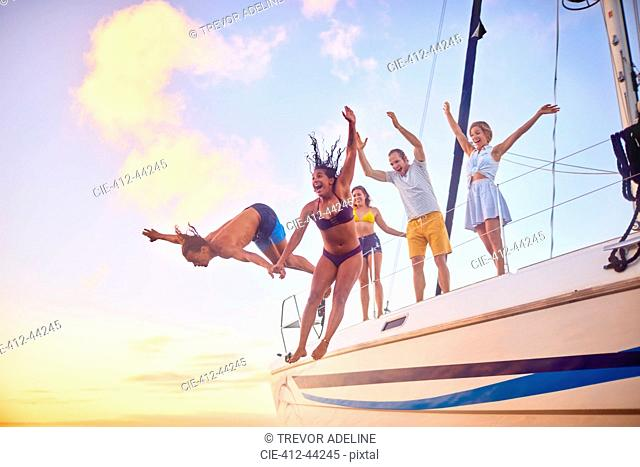 Playful friends jumping off boat