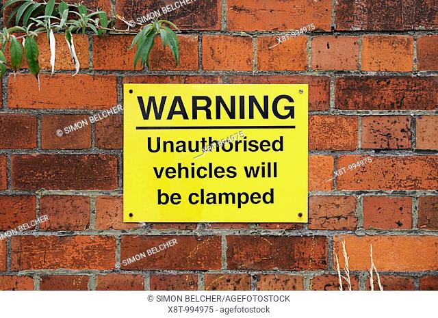 Vehicle Clamping Warning Sign  Oxford, United Kingdom  A sign in a private car park warns that unauthorized vehicles will be clamped  Clamping of vehicles on...