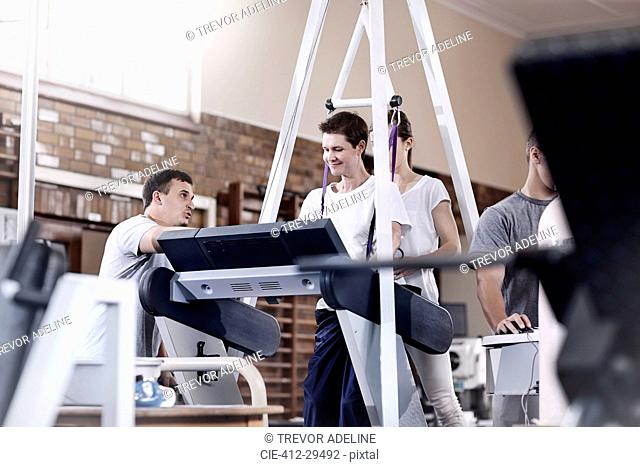 Physical therapists guiding man on treadmill