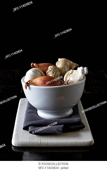 A bowl of shallots, garlic and ginger