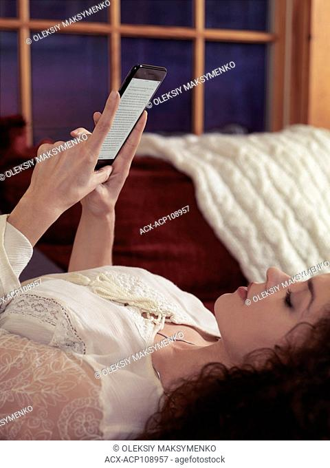 Woman reading book on iPhone 7 Plus at home lying on a sofa