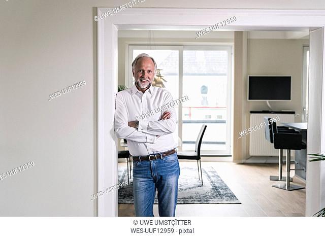 Portrait of smiling mature man leaning against door case in his apartment