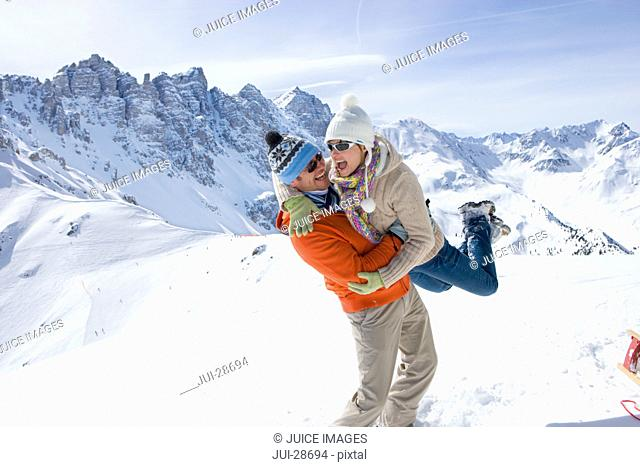 Man standing in snow lifting girlfriend with mountain in background