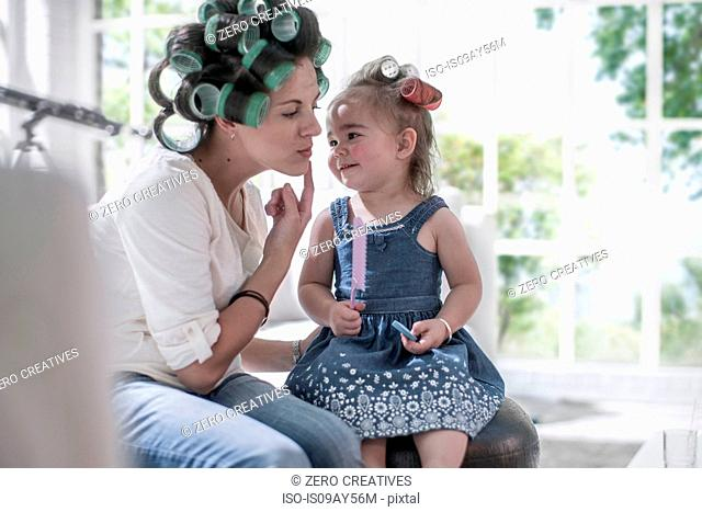 Mother in hair rollers pointing cheek to daughter