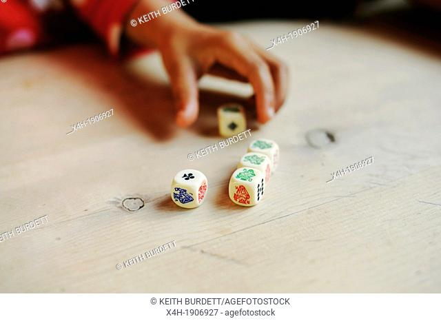 Young child playing poker or liar dice game,Wales