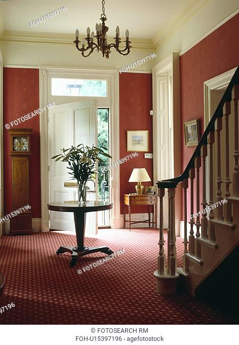 Antique circular table and patterned red carpet in red country hall