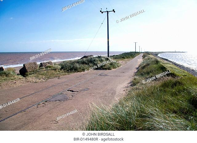 Road next to eroded railway line at Spurn Head, East Yorkshire, England, with North Sea on the left and Humber Estuary on the right