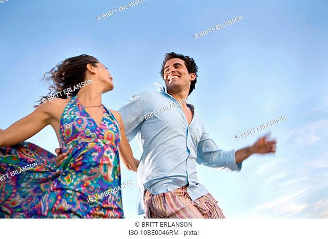 Loving couple running outside