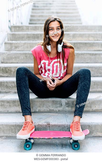 Portrait of teenage girl sitting on stairs with a skateboard and headphones