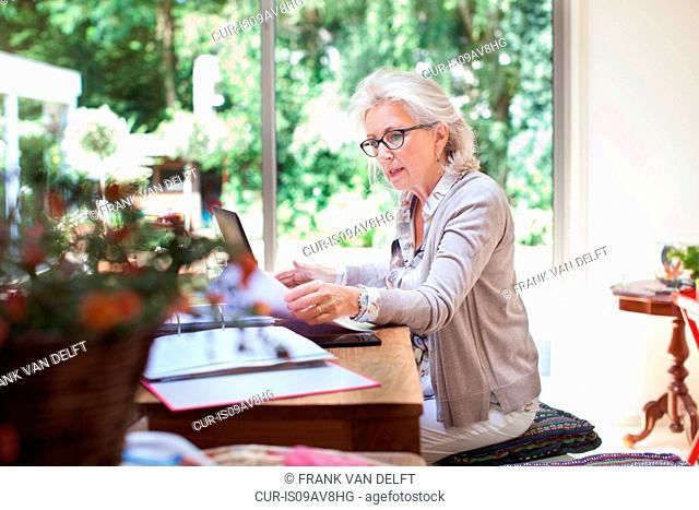 Senior woman sitting at table, looking through paperwork, using laptop