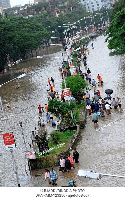 Monsoon ; people walking through flooded road heavy  rain in Parel ; Bombay Mumbai ; Maharashtra ; India