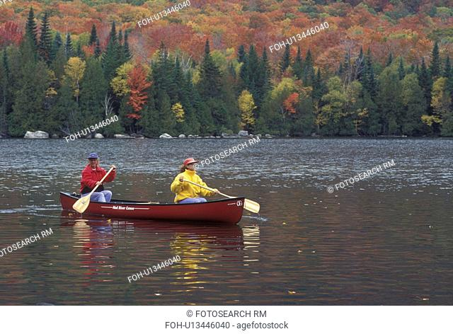 canoeing, canoe, Vermont, VT, Mother and daughter paddling a red canoe on Jobs Pond in Westmore in the fall