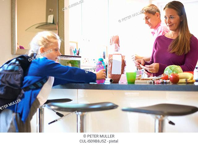 Schoolgirl pick up drink from kitchen counter