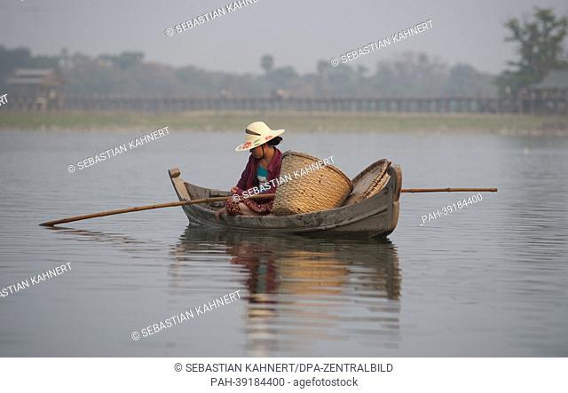A woman sits in her boar on Taungthaman Lake next to the U Bein Bridge in Amarapura, Myanmar, 02 April 2013. Photo: Sebastian Kahnert | usage worldwide