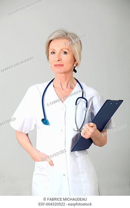 Closeup of senior nurse standing on white background