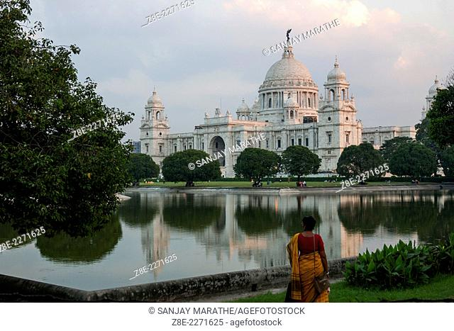 A woman in a saree walks along the water body at the Victoria memorial hall, an elegant, domed white marble edifice in Kolkata (Calcutta), West Bengal, India
