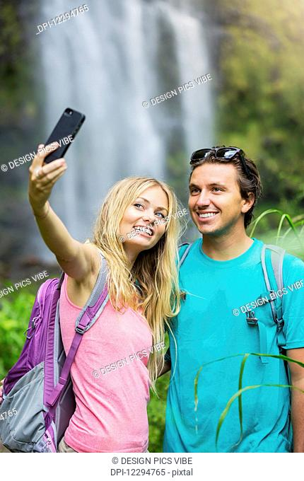 Couple having fun together outdoors. Taking self portrait with camera phone after hiking to incredible waterfall in Hawaii